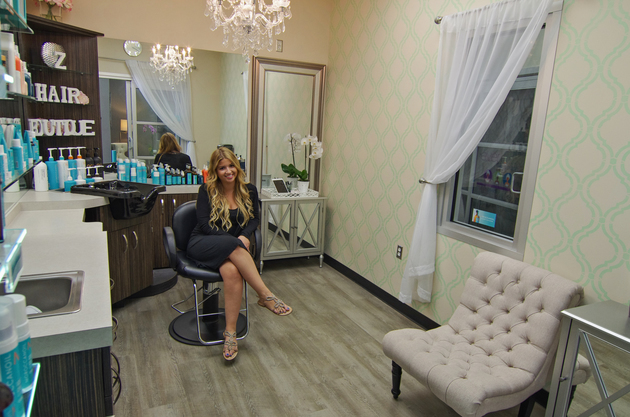 Sociable salon owner leans to the side in her chair eager to please her next client in her beautiful salon studio