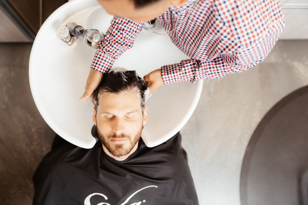 barber washes hair of comfortable client