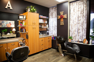 Large salon studio showing product shelving, custom cabintry, mirrors, salon chair, shampoo bowl, bright lighting at Sola Salon Studios hair salon in Longview