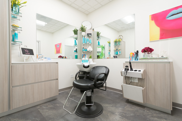 White single salon suite with pops of color on the walls and spacious storage.
