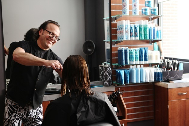 Experienced salon owner cheerfully cuts a woman