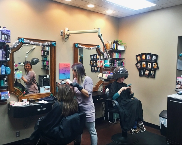 Colorful salon owner bonds with customer while dying her hair