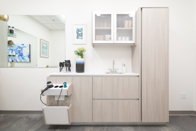 Studio interior including bright, spacious cabinetry, a sink, and a mirror