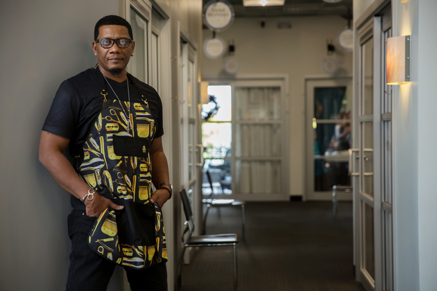 Confident barber stands in hallways at sola salon studios