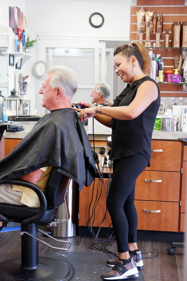 Experienced salon owner smiles as she cuts hair