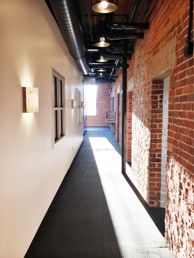 Industrial hallway with exposed brick and water fountains at Sola Salons South End