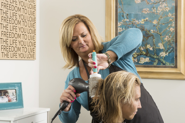 Close up of focused stylist blow drying client
