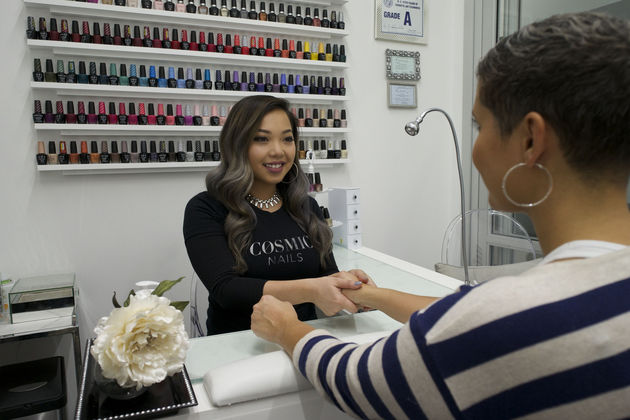 Friendly nail technician holds and evaluates customer