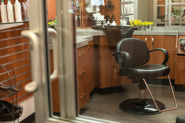 A look through the sliding glass door into a single suite equipped with a chair, a sink, and storage