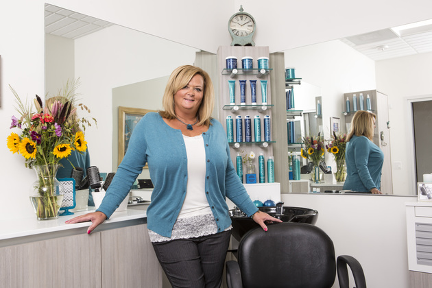 Welcoming salon owner stands with one hand on the counter and the other hand on her styling chair