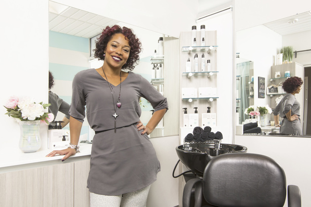 Confident salon owner posing inside her suite with one hand on the counter and the other on her hip.
