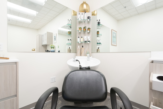 Single Sola salon wuite with blue decor, wood faced cabinetry, and products lining the shelves