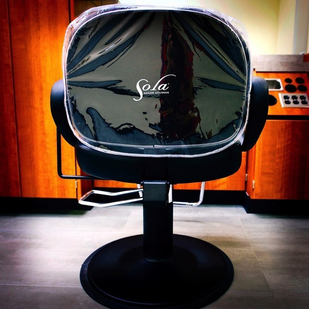 "Salon chair at Sola Salon Studios with plastic cover on it which reads ""Sola Salon Studios"" at hair salon in Longview"