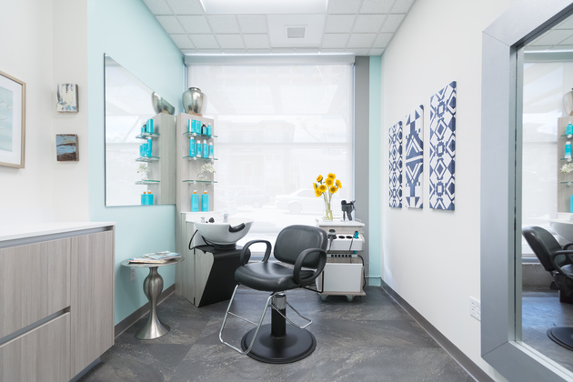 Single Sola salon suite with styling equipment, a large window, and blue decor