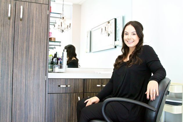 Relaxed salon owner leans back in her chair welcoming her next client