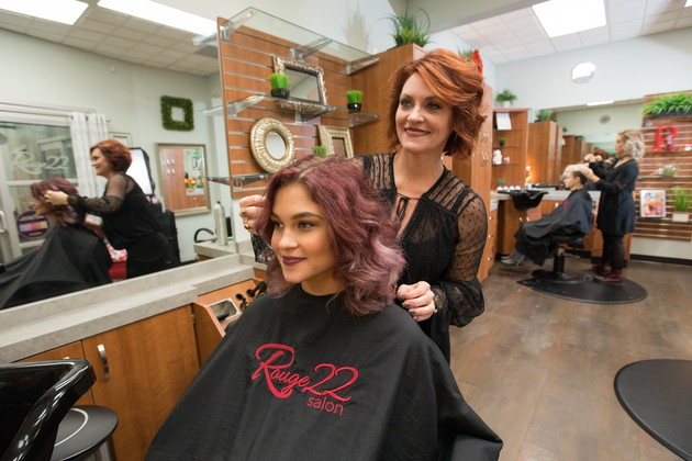 Friendly stylist adjusts happy customer