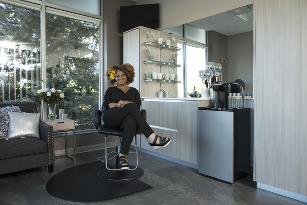 Smiling salon owner sitting in her styling chair with arms and legs crossed