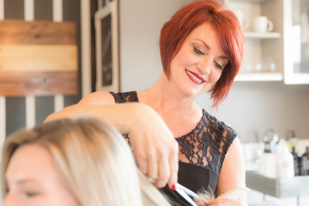 Close up of a smiling stylist cutting a woman