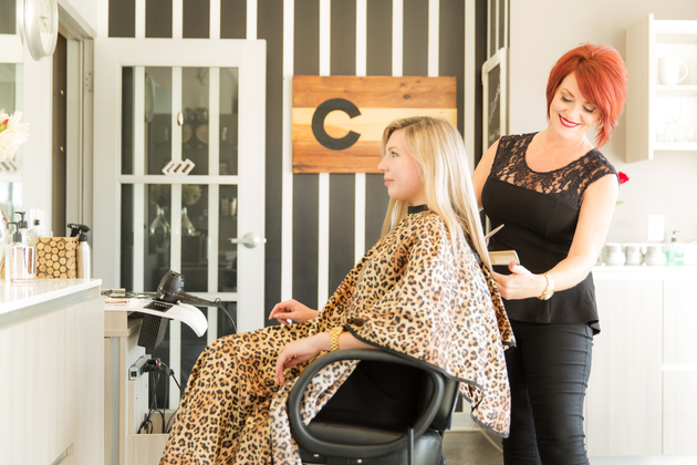 Hair stylist combing and cutting female blonde customer