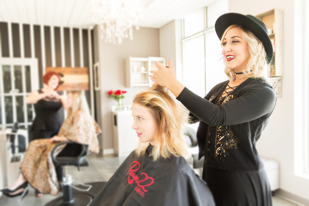 Comfortable salon owner stands behind the chair in her single suite leaning against the sink