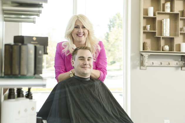 Hair stylist shows off her work to happy customer
