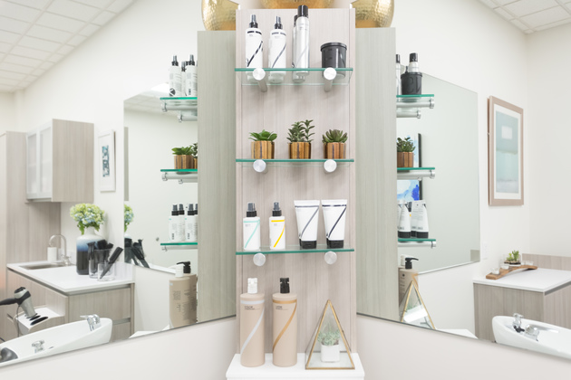 Shelves between two mirrors stacked with hair product