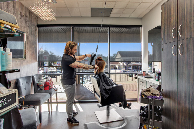 Stylist salon owner blow dries customers hair in front of large windows of a contemporary decorated suite