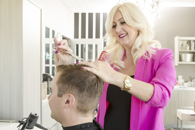 Closeup of a happy stylist cutting a man