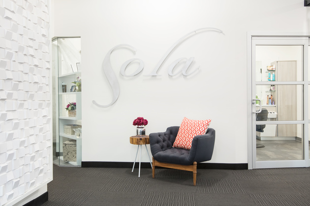 Entry way of Sola Salons at Blakeney. Well lit with a gray arm chair and flowers on a small side table.