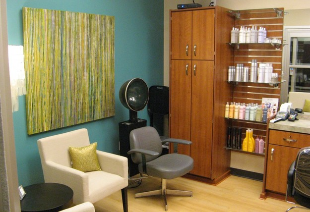 Pictured is a small sola salon studio space. This studio has aqua blue walls, a white upholstered chair with a lime pillow. There is a large abstract artwork behind the chair with greens and blue stripes. There is a chair with a dryer behind it. There are a lot of large cabinets and drawers with colorful salon products on the shelves.