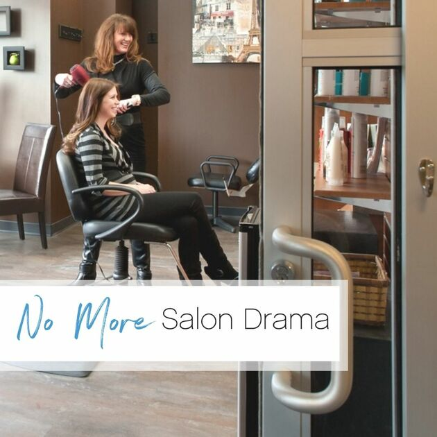 Stylist and client laugh together while blow drying the client