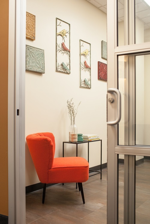A look through the sliding glass door into a decorated suite waiting area