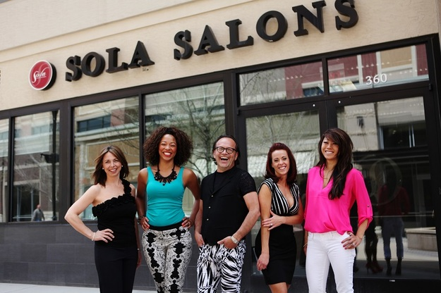 Five enthusiastic salon owners pose in front of a sola storefront