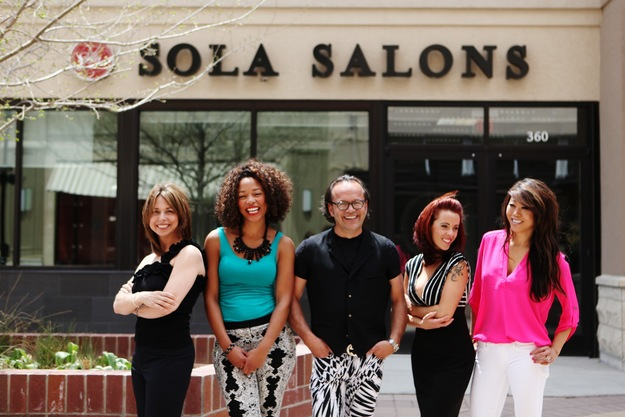 Five enthusiastic salon owners smile in front of a Sola storefront