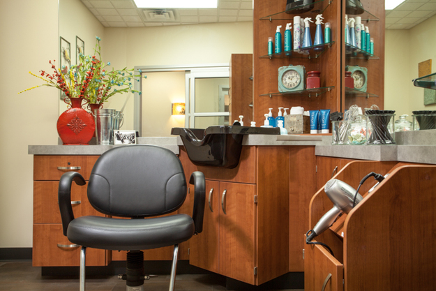Shampoo bowl, salon chair, and shampoo products. Tool cabinet with blow dryer and flat iron. Located inside Sola Salon in Tacoma, WA.