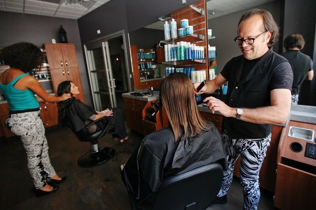 Two sociable stylist combing and cutting hair in modern suite