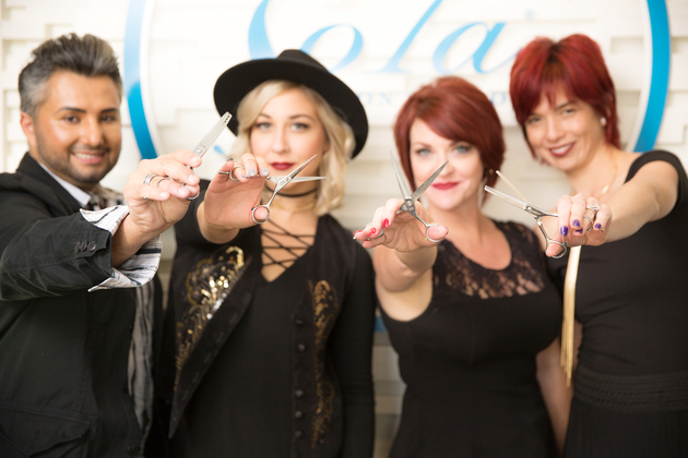 Four confident stylists holding shears in front of Sola logo