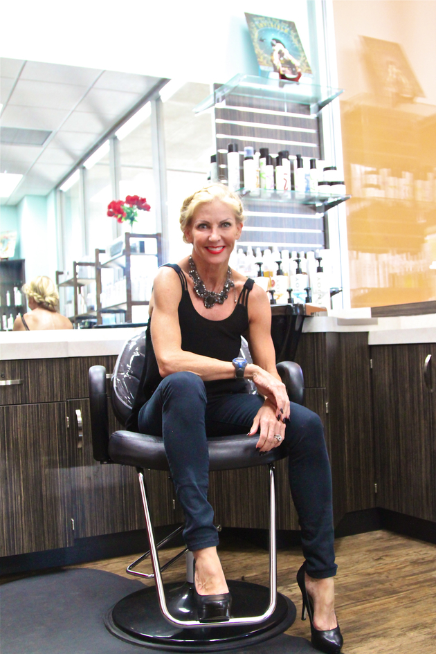 Eager stylist leans forward in her chair with her elbow leaning on her knee
