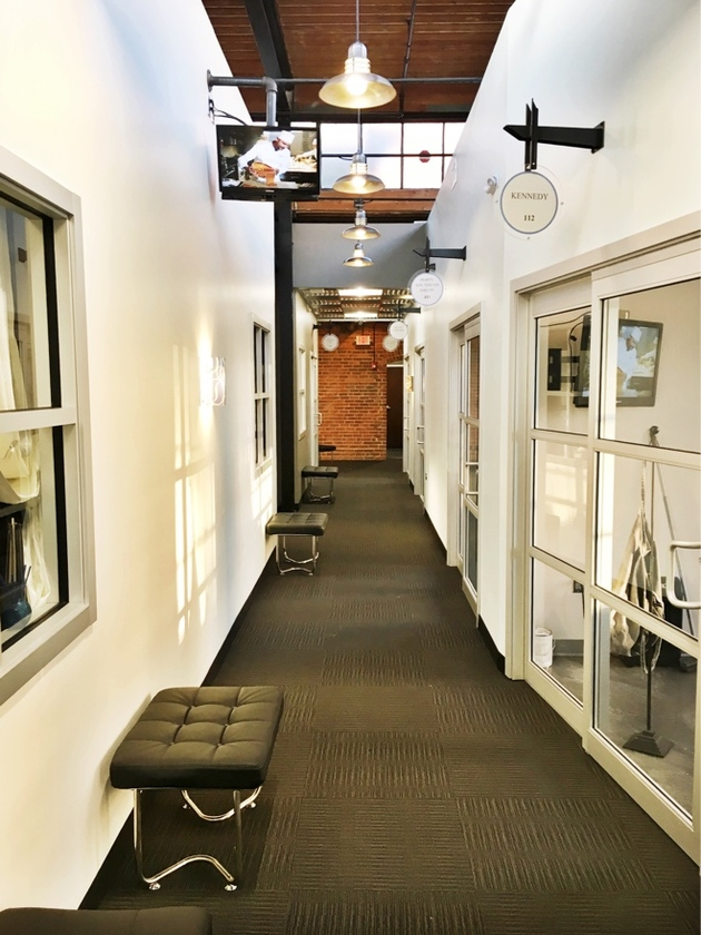 Industrial modern Sola hallway with glass sliding door studio entries and business signs above doorways and waiting areas along the wall