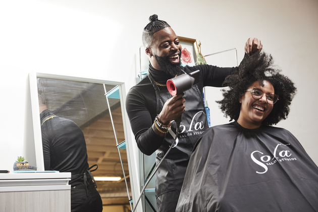 Happy stylist and client in a salon studio