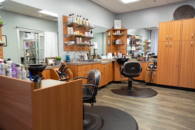 Large double studio at hair salon showing custom cabintry, salon chairs, shampoo bowls, mirrors and beautiful flooring at Sola Salon Studios in Longview