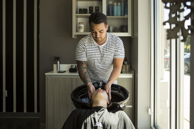 Focused male stylist shampoos a relaxed customer