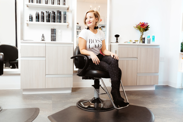 Happy and confident salon owner with her arms crossed in suite