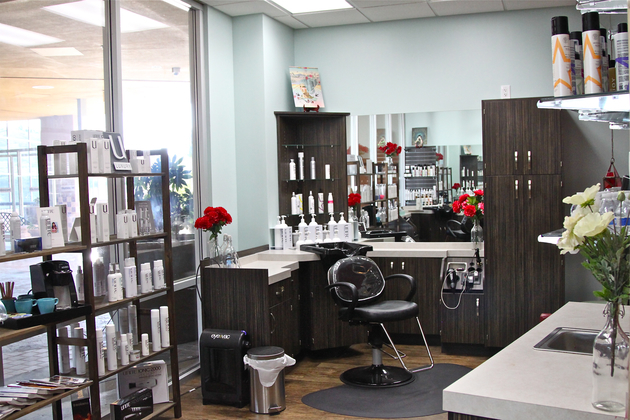 Salon studio with large windows, wood faced cabinetry, products lining the shelves, and splashes of red and white flowers.
