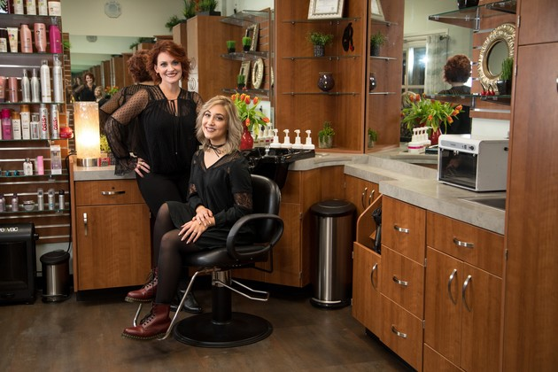 Two women look into the camera from a clean salon studio