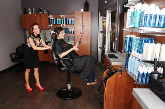 Cheerful stylist consults sitting customer whom is pointing to a magazine