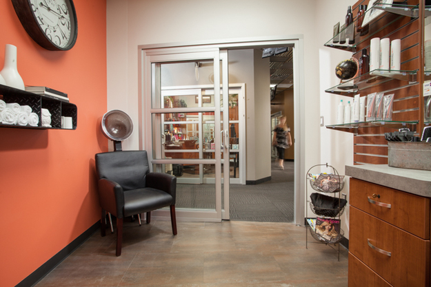 A tastefully decorated room inside Sola Salon in Tacoma. Featured is a drying station, shampoo bottles and studio cabinetry.