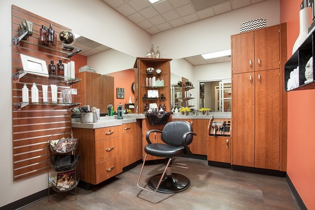 Decorated single suite interior with chair, wood cabinets, mirrors, and plenty of storage