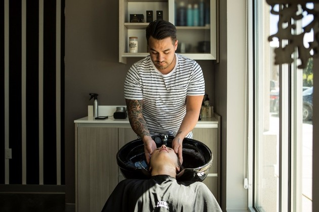 Male stylists shampoos relaxed clients hair as sunlight pours in through the studio