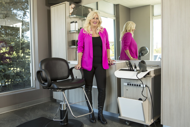 Happy stylist standing in her suite with one hand on chair and the other hand on the counter